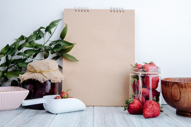 Side view of a sketchbook with strawberry jam in a glass jar and fresh ripe strawberries in a glass jar on rustic Free Photo