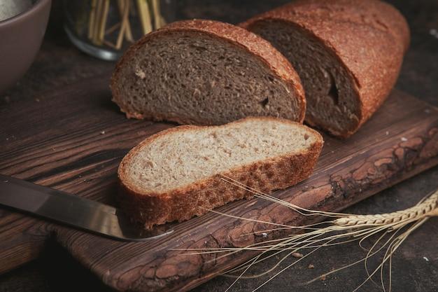 Ломтики вида сбоку хлеба с ножом на разделочную доску и темно-коричневый. Бесплатные Фотографии