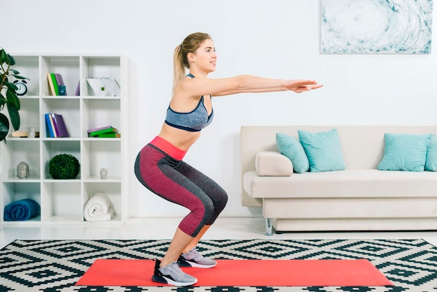 Side view of slim fitness young woman practicing exercise at home