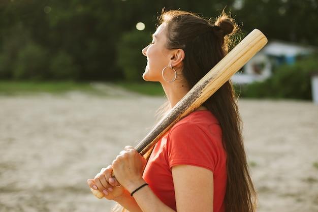 Side view smiley girl holding baseball bat Free Photo