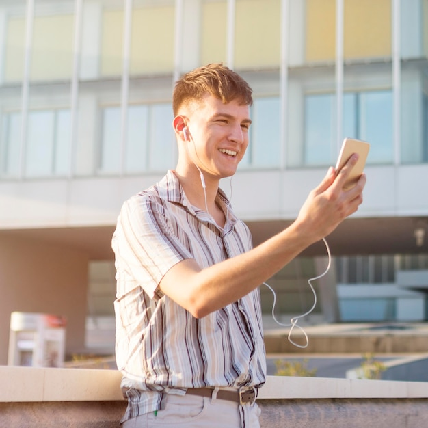 Side view of smiley man having a video call outdoors Free Photo