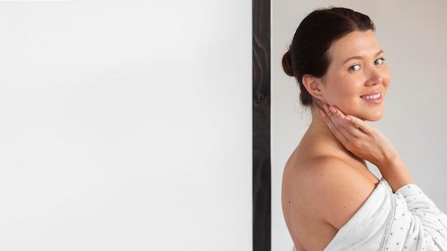 Vista laterale della donna sorridente in accappatoio dopo la cura di sé Foto Gratuite