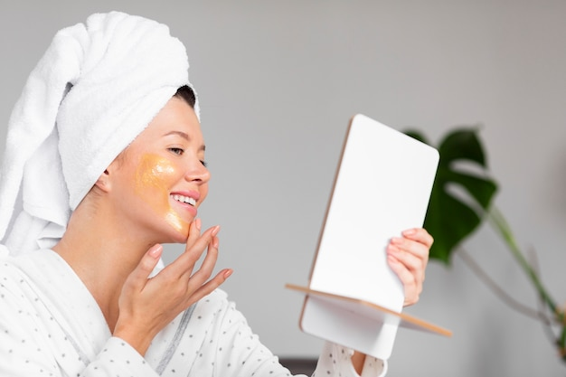 Side view of smiley woman in bathrobe applying skincare Free Photo