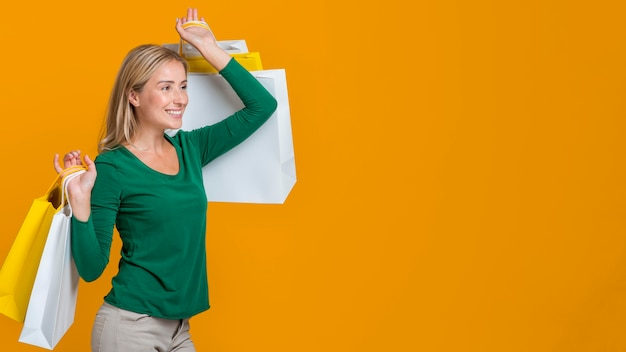 Side view of smiley woman carrying many shopping bags Free Photo