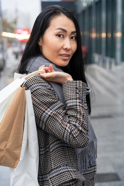 Donna di smiley vista laterale che tiene i sacchetti Foto Gratuite