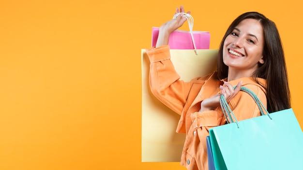 Vista laterale della donna sorridente che sostiene i sacchetti della spesa Foto Gratuite