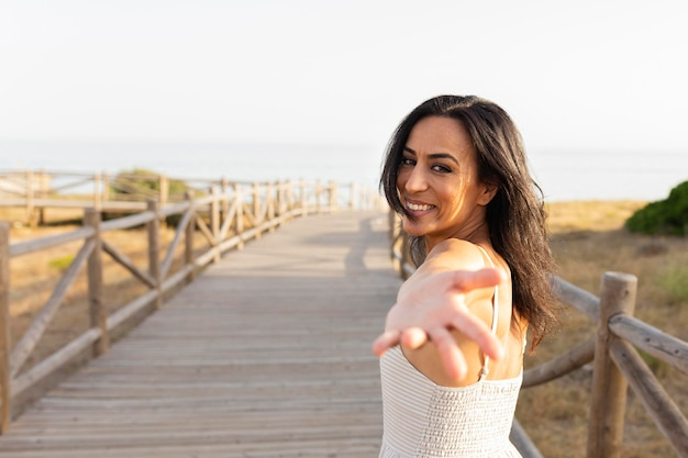 Side view of smiley woman posing outdoors with hand reaching Free Photo