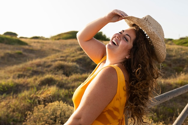 Side view of smiley woman posing outdoors Free Photo