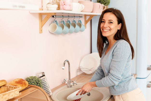 Side view smiley woman washing the dishes Free Photo
