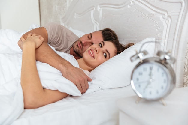 Side view of smiling lovely couple sleeping together in bed Free Photo