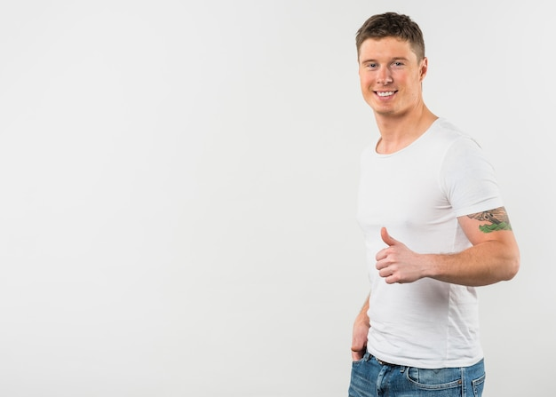 Side view of a smiling young man showing thumb up sign against white background Free Photo