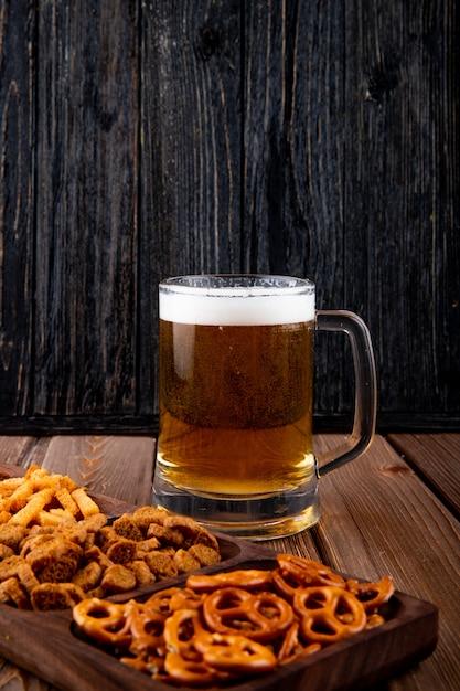 Вид сбоку закуски к пиву жареные чипсы и мини-брезель с кружкой пива на деревянном столе Бесплатные Фотографии