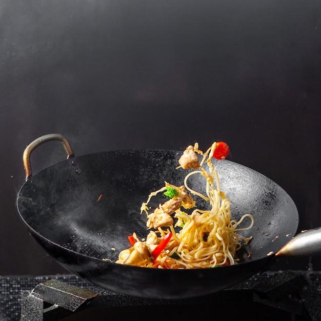 黒い背景にフライパンでサイドビュースパゲッティ。 無料写真