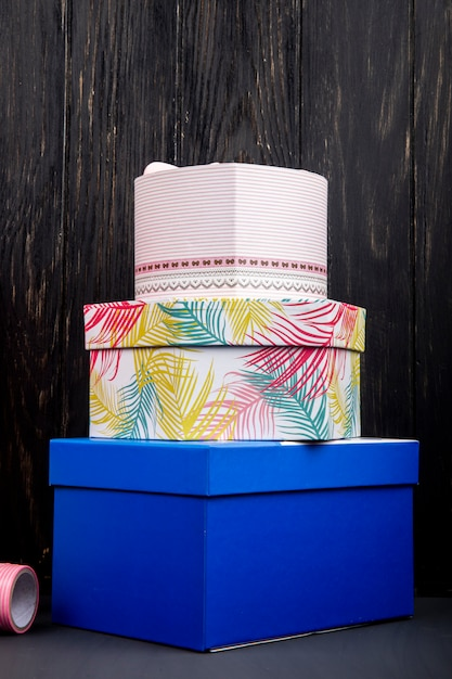Side view of a stack of colorful present boxes at dark wooden table Free Photo