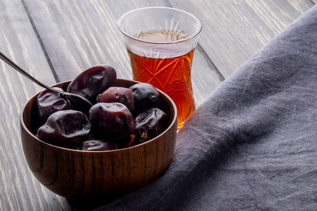 Side view of sweet dried date fruit in a bowl with armudu glass of tea on a wooden rustic Free Photo