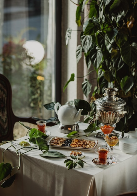 Side view of a table served with tea and nuts and dried fruits in a plate Free Photo