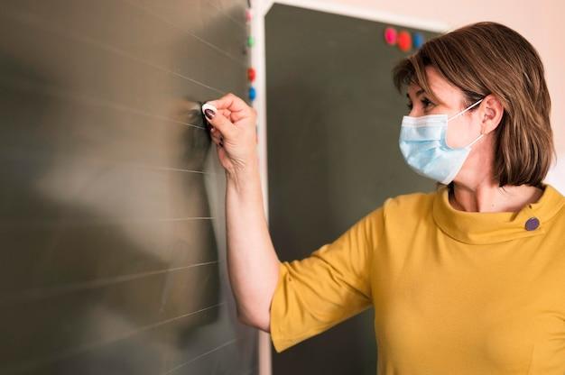 Учитель вид сбоку с маской, пишущей на доске Бесплатные Фотографии