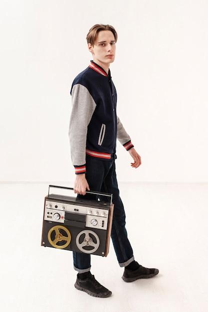 Вид сбоку подросток, держащий кассету Бесплатные Фотографии