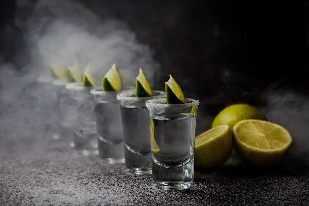 Side view tequila in a glass served with limes and salt Free Photo