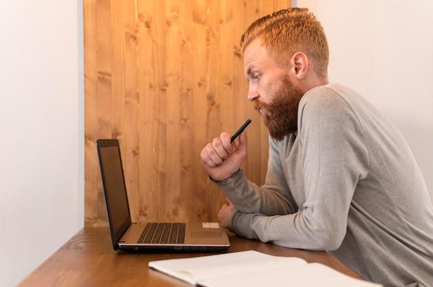 Uomo premuroso di vista laterale che esamina il suo computer portatile Foto Gratuite