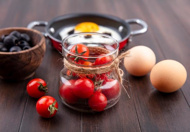 Vista laterale di pomodori in vaso di vetro con uova ciotola di oliva nera e padella di uovo fritto su legno Foto Gratuite