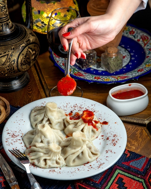 Side view of traditional georgian khinkali and a woman hand holding a spoon with spicy tomato sauce Free Photo