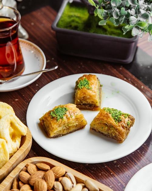 Боковой вид турецкой пахлавы с орехами и стаканом чая Бесплатные Фотографии