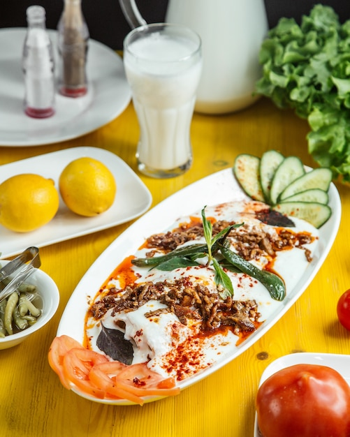 Side view of turkish iskender kebab served with sour yogurt sliced cucumbers and tomatoes on white plate Free Photo
