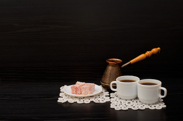 Side view of two cups of coffee on the lace napkins, turkish dessert and pots Premium Photo