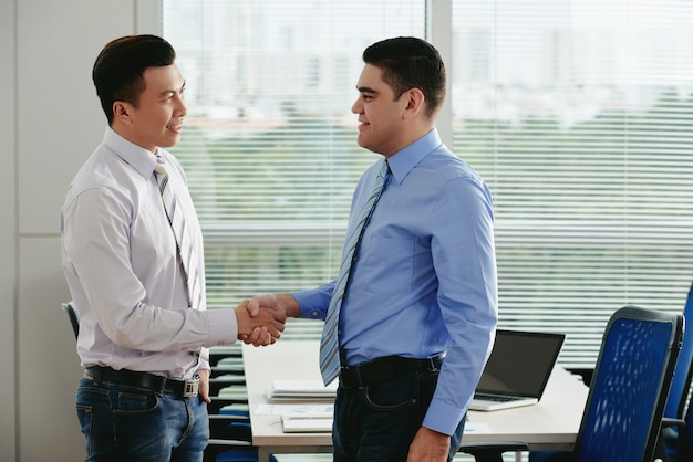Side view of two managers giving a handshake to greet each other in the office Free Photo