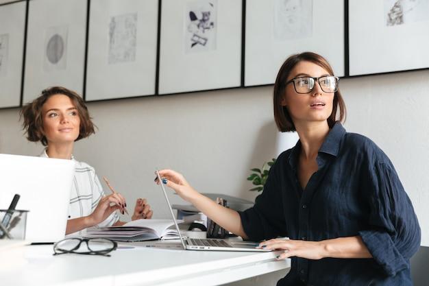 Vista laterale di due belle donne sedute al tavolo Foto Gratuite