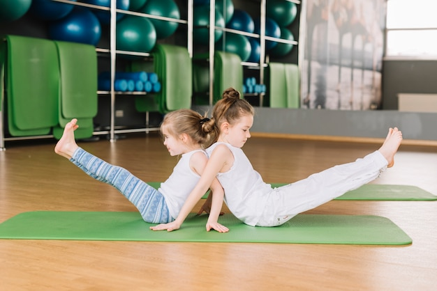 Side view of two small girl child doing yoga exercises Free Photo
