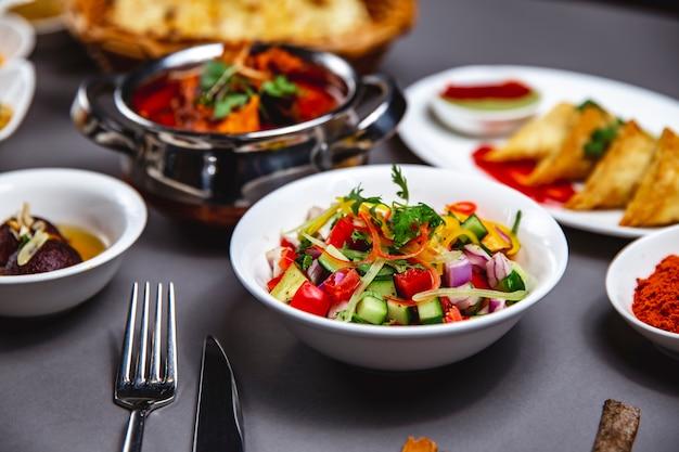 キュウリ赤玉ねぎピーマングリーンと黒コショウプレートのサイドビュー野菜サラダ 無料写真