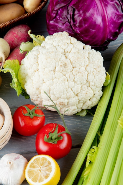 Side view of vegetables as cauliflower celery tomato cabbage garlic with cut lemon on wooden background Free Photo