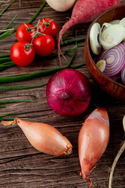 Side view of vegetables as shallot onion tomato and others on wooden background Free Photo