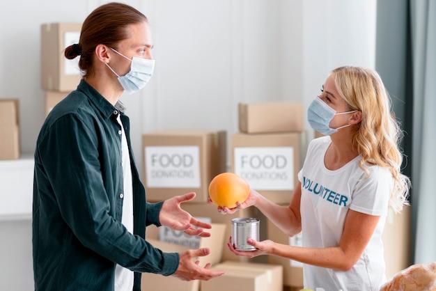 Vista laterale del volontario che distribuisce cibo come donazione Foto Gratuite