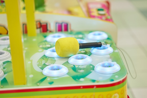 Side view of whack a mole with hammer for playing in game arcade Premium Photo