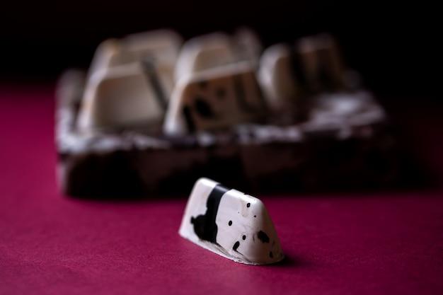 Вид сбоку белый в черном пятнышке шоколадные конфеты на столе Бесплатные Фотографии