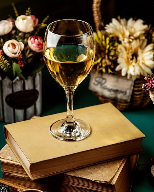 Vista laterale di vino bianco in vetro sul libro Foto Gratuite