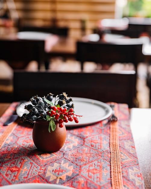 Bacche selvatiche di vista laterale in un vaso di argilla sul tavolo Foto Gratuite