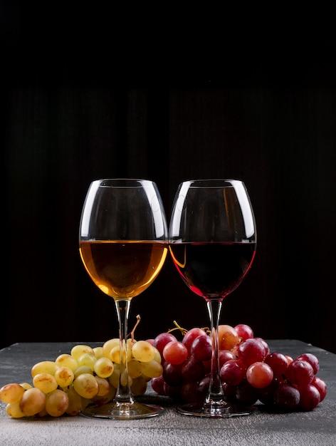 Бокалы для вина с виноградом на черном фоне Бесплатные Фотографии