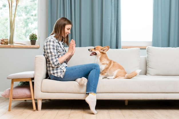 Side view of woman asking dog to high-five Free Photo