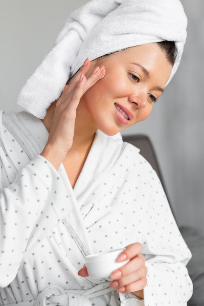 Side view of woman in bathrobe and towel applying cream Free Photo