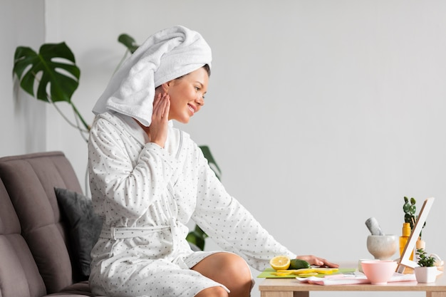 Side view of woman in bathrobe using skincare Free Photo