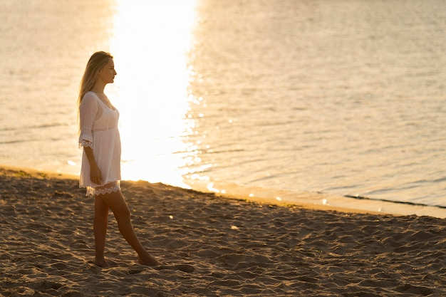 Side view of woman on beach at sunset Free Photo