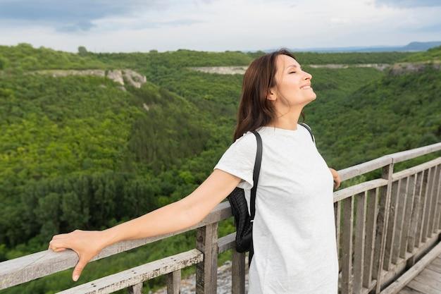 Side view of woman on bridge enjoying nature Free Photo