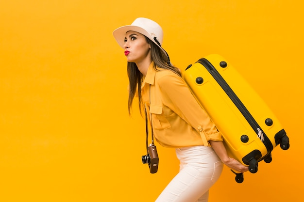 Side view of woman carrying luggage and camera with copy space Free Photo