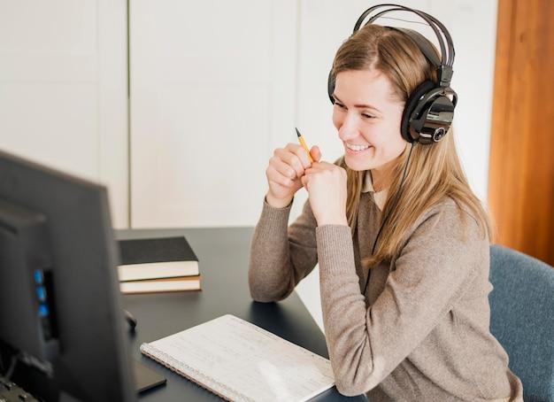 Vista laterale della donna allo scrittorio con le cuffie che partecipano alla classe online Foto Gratuite