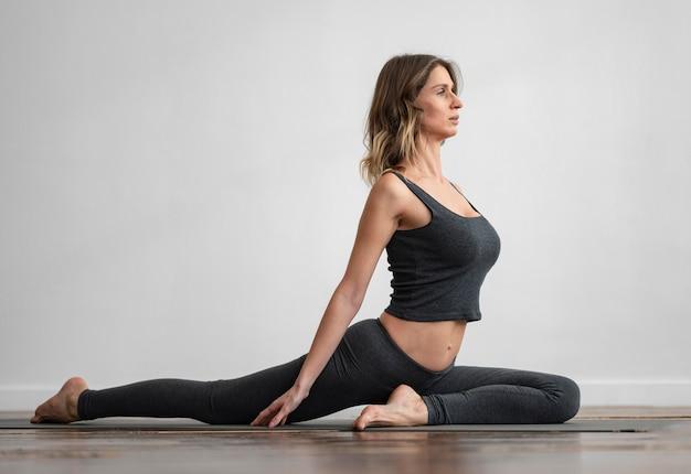 Vista laterale della donna che fa yoga a casa sulla stuoia Foto Gratuite