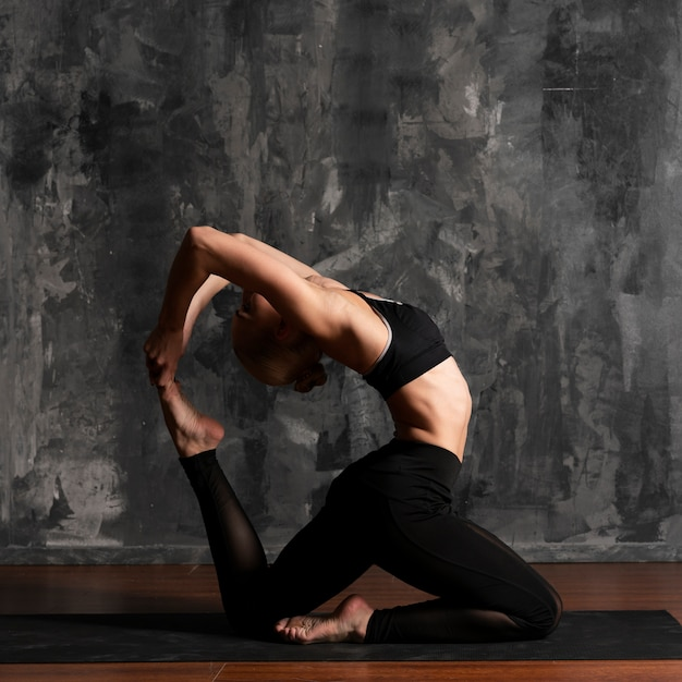 Side view woman doing yoga with stucco background Free Photo
